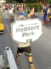 A citizen holding up a sign that reads 'Hubbard Park'