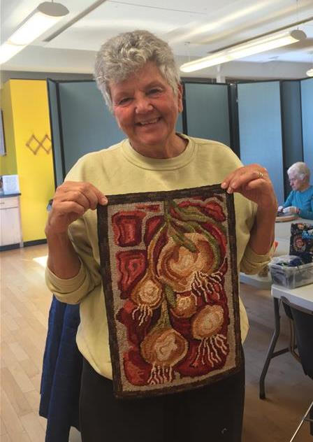 Rug hooking student shows off her work.