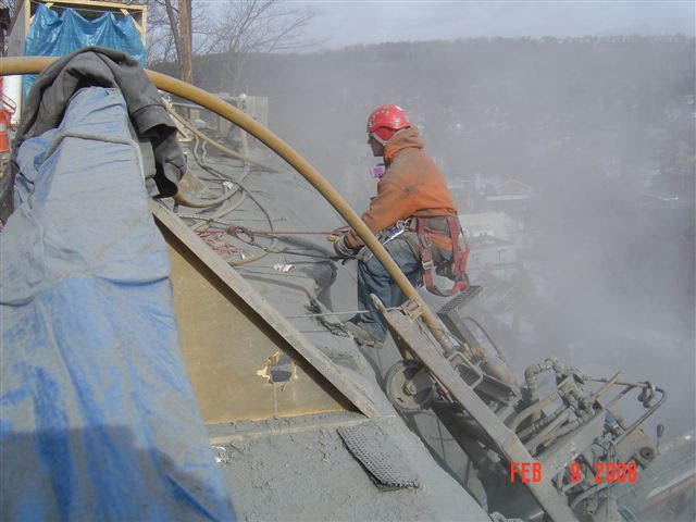 A worker lowering himself to the cliffside structure
