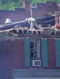 Construction worker works on roof of a damaged building.