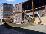 A backhoe helps in the demolition of buildings.