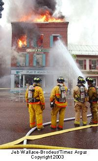 Firefighters work to extinguish the building on fire.